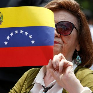 A woman holds up a Venezuela flag during a protest of civil organizations in support of Venezuelan President Nicolas Maduro's government, in Mexico City