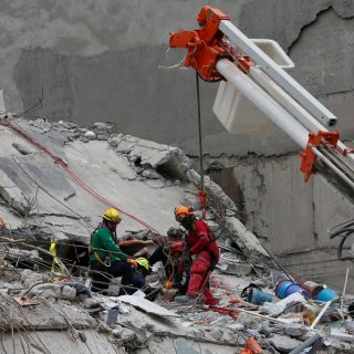 Members of Israeli and Mexican rescue teams search for survivors in the rubble of a collapsed building in Roma neighbourhood after an earthquake in Mexico City