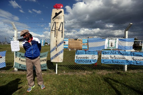 A man stands in front of signs in support of the missing crew members of the ARA San Juan submarine in Mar del Plata